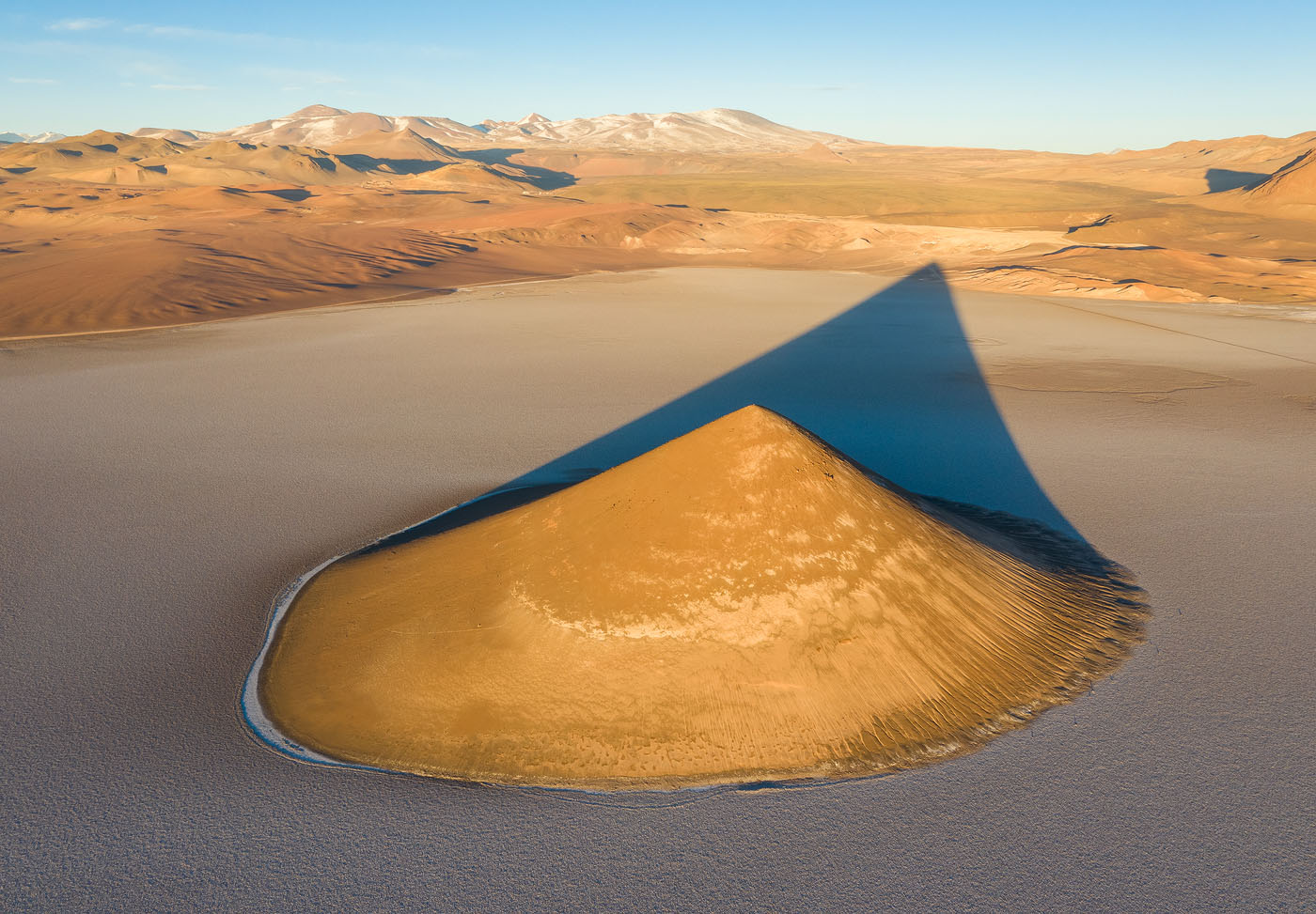 Cono Arita is a sandstone hill in the middle of the Arizaro salt flat in the Argentinean Puna (high-altitude desert). When morning light strikes, the beautiful shadow is cast upon the plain. Taking the drone up allowed me to show this, while creating separation between the cone, its shadow and the surrounding hills and mountains.
