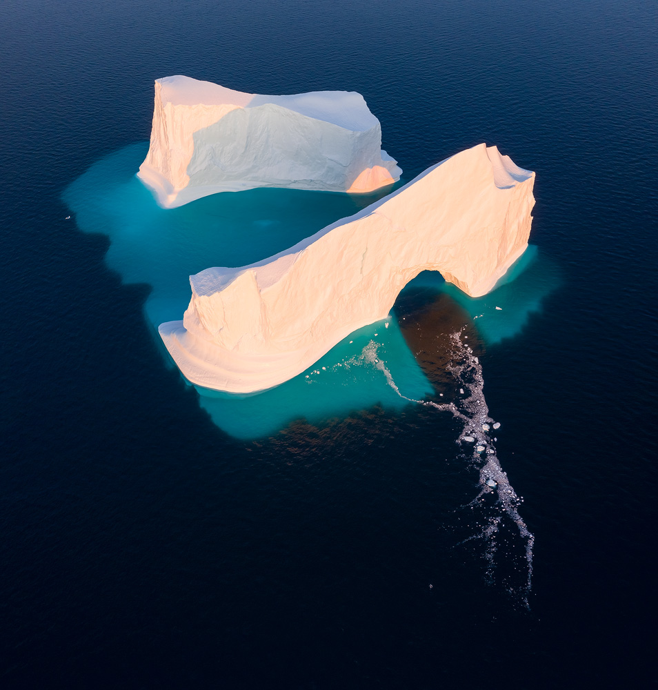 A gigantic iceberg floating in Disko Bay, Greenland. The position of the iceberg meant it was impossible to get separation of its two parts when still showing the light passing through the arch and hitting the back segment from the water level. Another clear advantage is the fact that the submerged part of the iceberg is beautifully showing, in addition to debris from a recent collapse in the arch.