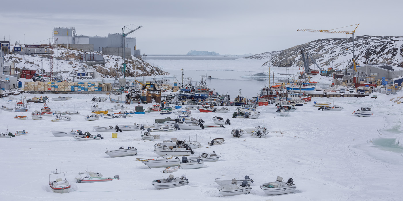 Ilulissat harbor in winter. The boats are resting on sea ice.