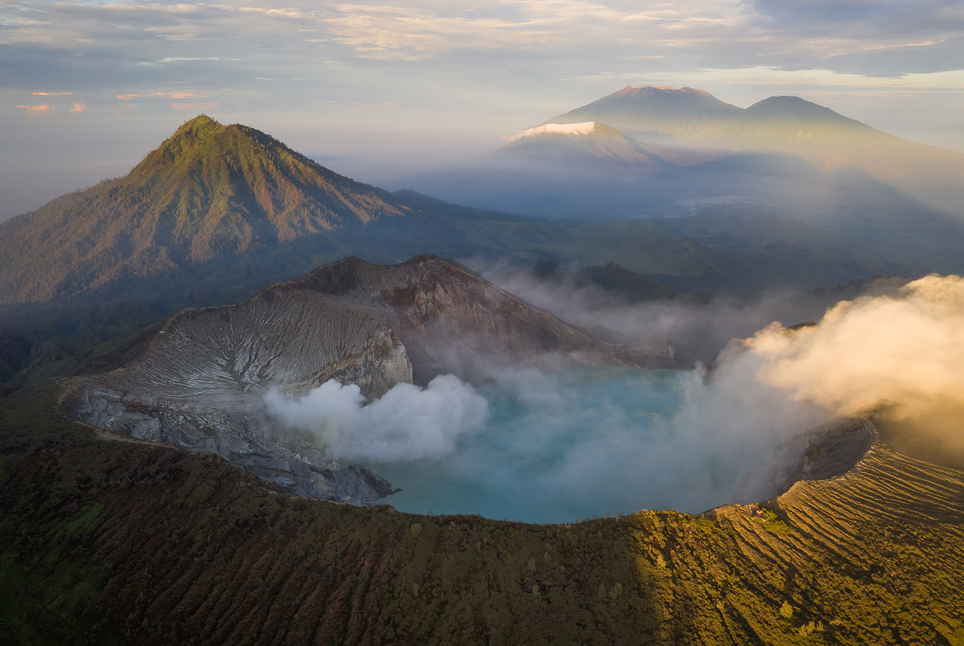 Astounding sunrise light shines upon five East Javanese volcanoes. In the bottom of the frame is Ijen crater. To its left, the lush, green Gurung Ranti. Then farther away, from left to right: Pendil, Raung and Suket. The shadow from the bottom-left to the mid-right is cast by Gurung Merapi, just behind me. This is a classic near-far landscape shot, which demonstrates that the approach to aerial photography is often very similar to that of regular photography from the ground. My foreground/background compositional considerations were identical.