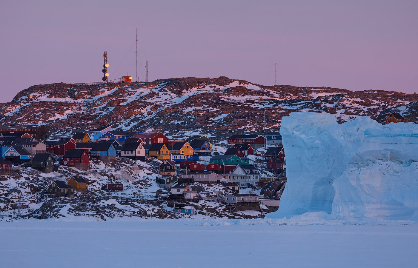 Houses in Uummannaq and an iceberg stuck in sea ice next to town