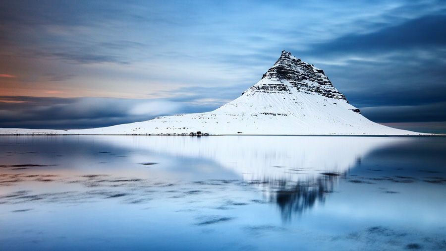 Mount Kirkjufell reflects on the calm waters of the lagoon below it