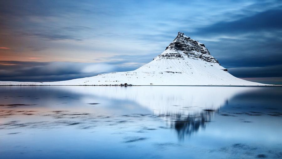 Mount Kirkjufell reflects on the calm waters of the lagoon below it