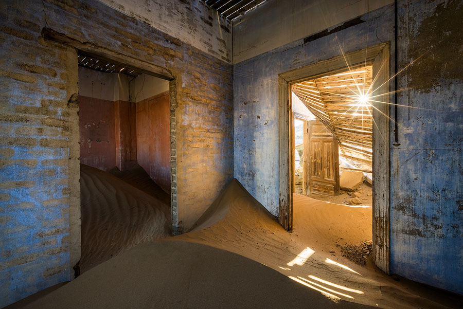 The sun peeks in through the collapsed roof at a beautiful, less visited room